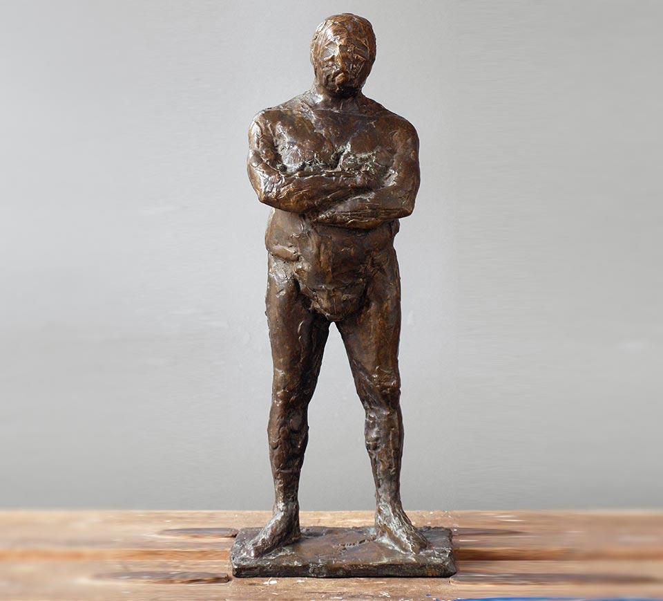 Stehende männliche Figur mit verschränkten Armen